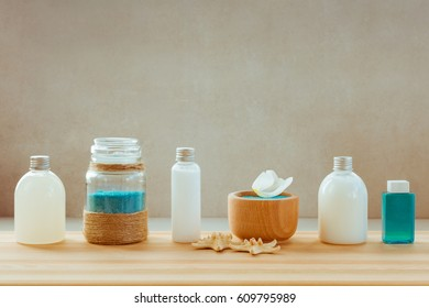 Spa or wellness setting in blue and white colors. Bottles with essential aroma oil, shampoo, towels, sea salt on neutral background.