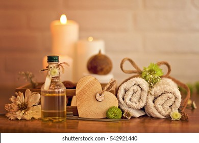 Spa and wellness setting with bottle of oil, candles and towels and dry flowers