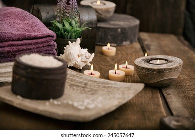 Spa and wellness setting with natural bath salt, candles, towels and flower. Wooden dayspa nature set