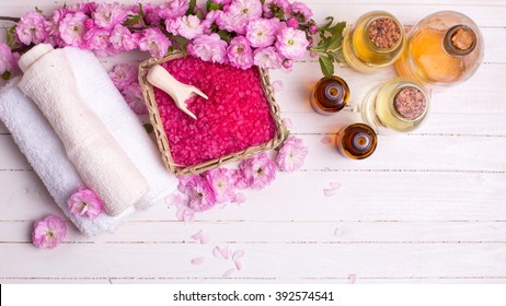 Spa or wellness setting. Pink sea salt in bowl, bottles with aroma oils  and pink flowers on white  wooden background. Selective focus is on salt. Place for text.
