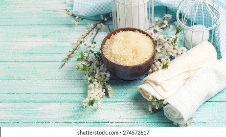 Spa and wellness setting. Sea salt in bowl, towels, candles and  flowering branches of trees on turquoise painted wooden background. Selective focus.Toned image.