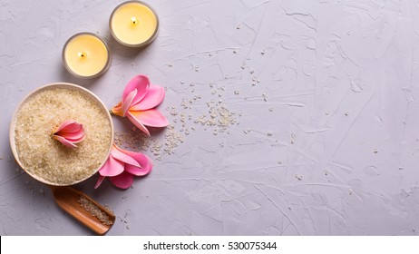 Spa or wellness setting in yellow color. Sea salt in bowl, candles and flowers on grey textured background. Selective focus. Place for text. Flat lay.