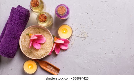 Spa or wellness setting in yellow and violet colors. Bottles with aroma oil, sea salt in bowl, towel and flowers on grey background. Selective focus. Place for text.