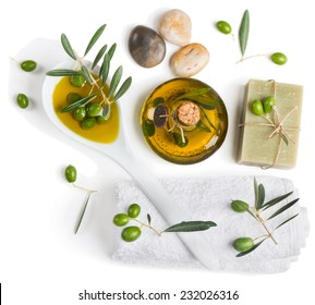 Spa and wellness setting with zen stone, olives and towel on white background, top view.