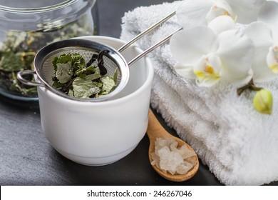 Spa and wellness - towel, orchid flowers, salt, herb tea on dark stone background