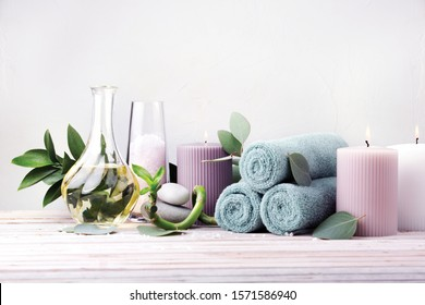 Spa in winter colors. Bath concept. Oil for body massage, lavender sea salt, towels, fresh bamboo, candles, sea stones and eucalyptus leaves on a light wooden background. Copy space