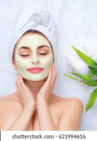 Spa Woman applying Facial clay Mask. Beauty Treatments. Close-up portrait of beautiful girl with a towel on her head applying facial mask.