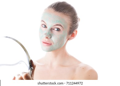 Spa Woman applying Facial clay Mask. Beauty Treatments. Close-up portrait of beautiful girl applying facial mask