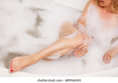 Spa Woman. Beautiful Girl in the Bath Touching Her legs. Perfect Skin. Skincare. Young Skin