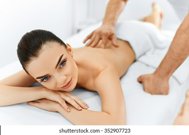 Spa Woman. Beauty Treatment. Beautiful Young Healthy Caucasian girl relaxing with hand Massage Procedure In The Spa Salon. Masseur Massaging her Back. Body Care. Skin Care, Wellness, Wellbeing.