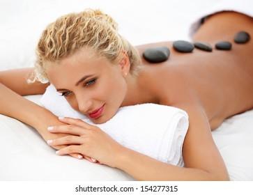 Spa Woman. Close-up of a Beautiful Woman Getting Spa Treatment. Stone Massage
