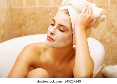 Spa woman with cream lotion on face relaxing in bath