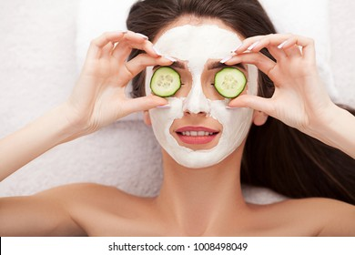 Spa. Woman with facial mask and cucumber slices in her hands