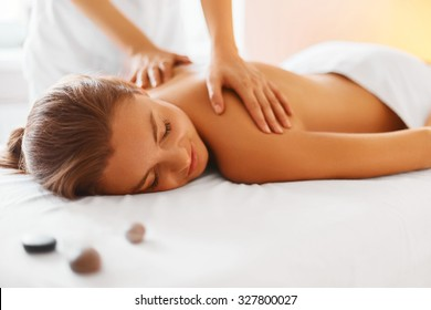 Spa woman. Female enjoying relaxing back massage in cosmetology spa centre. Body care, skin care, wellness, wellbeing, beauty treatment concept.