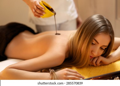 Spa Woman. Young Woman Gets Chocolate Body Mask at Beauty Salon
