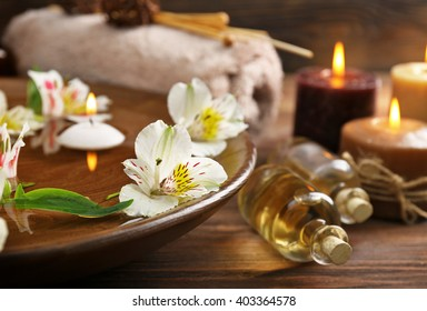 Spa wooden bowl with water and flowers closeup
