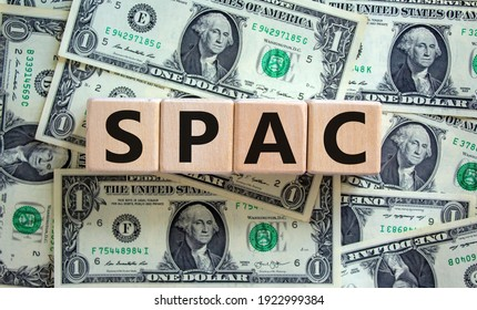 SPAC, special purpose acquisition company symbol. Wooden cubes with word 'SPAC' on beautiful background from dollar bills, copy space. Business and SPAC, special purpose acquisition company concept.