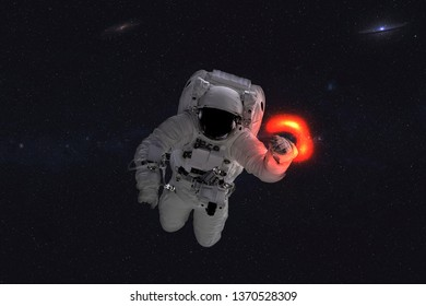 Space astronaut near black hole red glow. Space adventure in outer space. Science fiction. Elements of this image were furnished by NASA