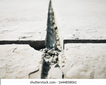 space in concrete floor, expansion joint or movement joint is an assembly designed, pipelines expand and contract due to warming and cooling from seasonal variation, photo is Depth of field style