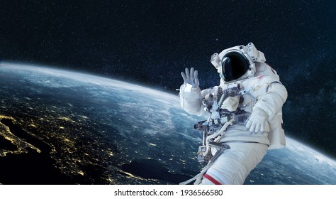Space man astronaut greets and waves his hand in space on a background of the blue planet Earth. Space mission wallpaper, concept. Welcome to space