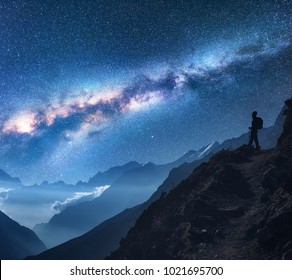 Space with Milky Way, girl and mountains. Silhouette of standing woman on the mountain peak, mountains and starry sky at night in Nepal. Sky with stars. Trekking. Night landscape with bright milky way