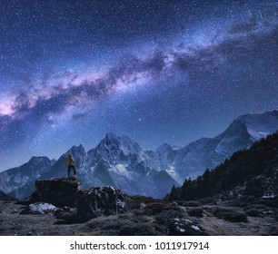 Space with Milky Way and mountains. Standing man on the stone, mountains and starry sky at night in Nepal. Rocks with snowy peaks against sky with stars. Trekking.Night landscape with bright milky way