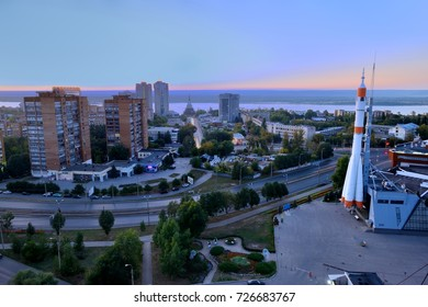 Space rocket. Beautiful buildings of the city of Samara in the rays of the setting sun. Russia.