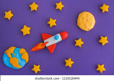Space Rocket Flying To The Moon Through The Starry Sky. Space rocket and planet Earth with the Moon are made out of play clay (plasticine).