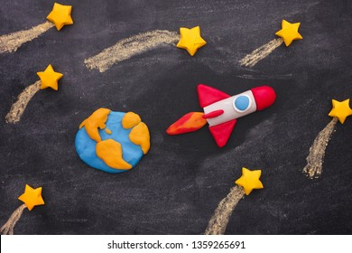 Space Rocket Flying Through The Shooting Stars. Space rocket and planet Earth are made out of play clay (plasticine).