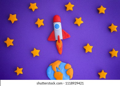 Space Rocket Flying Through The Starry Sky. Space rocket and planet Earth are made out of play clay (plasticine).