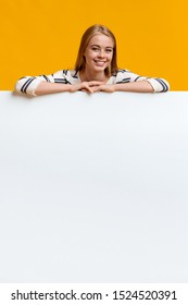 Space for your ad. Smiling teenage girl leaning on blank white board over orange background.