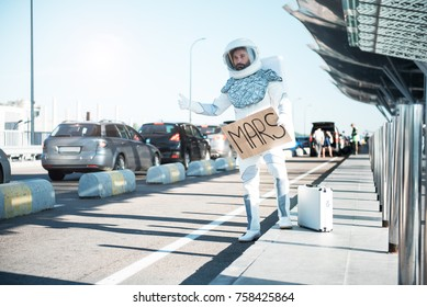"Spaceman wearing strange armor is asking for a ride, holding a cardboard sign with the word ""Mars"" written on it. Full length portrait. Copy space on left side."