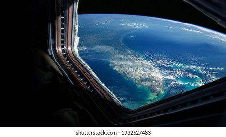 Spaceship flies near the amazing blue planet earth, view from the window. Travel and tourists in space, concept. Beautiful space view of the Earth with cloud formation. Hotel in space