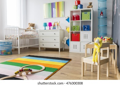 Spacious baby room with minimalistic furniture, toys and colorful decorations