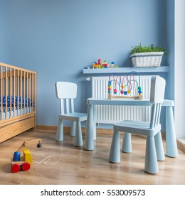 Spacious baby room with wooden furniture, cot, blue walls and wooden floor panels