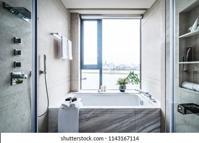 Spacious bathroom in gray tones with heated floors, freestanding tub, walk-in shower, double sink vanity and skylights.