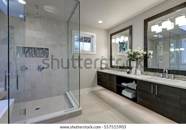 Geräumiges Badezimmer in Grautönen mit beheiztem Fußboden, begehbare Dusche, Doppelwaschbecken und Oberlichter.  Nordwesten, USA