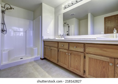 Spacious bathroom interior with open shower. Wooden cabinet with large mirror