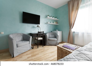 Spacious bedroom in blue color with television and armchairs