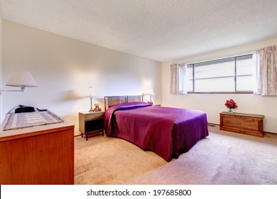 Spacious bedroom with carpet floor, white wall. Furnished with old wooden furniture