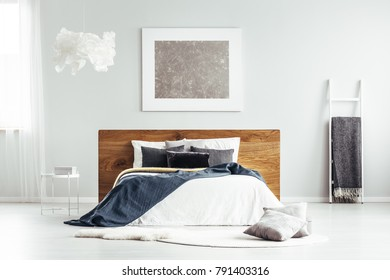 Spacious bedroom interior with cloud lamp, white ladder with and simple bed with wooden bedhead, blankets and cushions