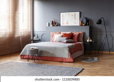 Spacious bedroom interior with a comfy bed, pillows, lamp, painting, rug and window blinds