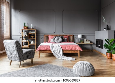 Spacious bedroom interior with pouf and gray armchair in front of a pink bed with wooden bedhead. Real photo