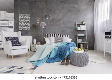 Spacious bedroom in new style with white furniture, window and decorative wall finish