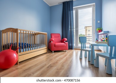 Spacious blue baby room with cot, armchair, balcony, window curtain, small table and chairs