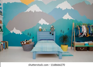 A spacious boy bedroom with a beautiful turquoise and grey mountain wall mural and bookshelves