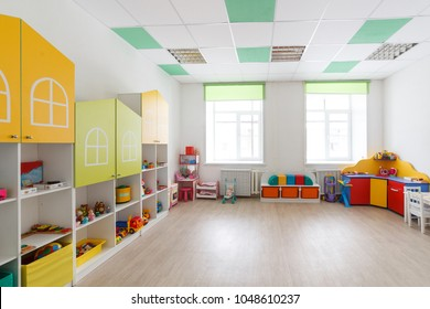 Spacious bright game room in the kindergarten with toys, two large windows and tables for classes. Natural light.