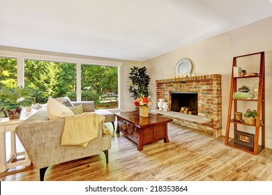 Spacious bright living room with brick fireplace, couch, wooden coffee table and glass wall