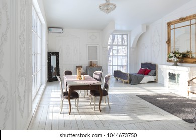 A spacious bright living room with a stylish modern design with elements of antique decor and beautiful chic old style furniture