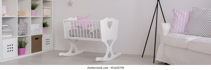 Spacious child room in white with cradle, shelving unit and sofa